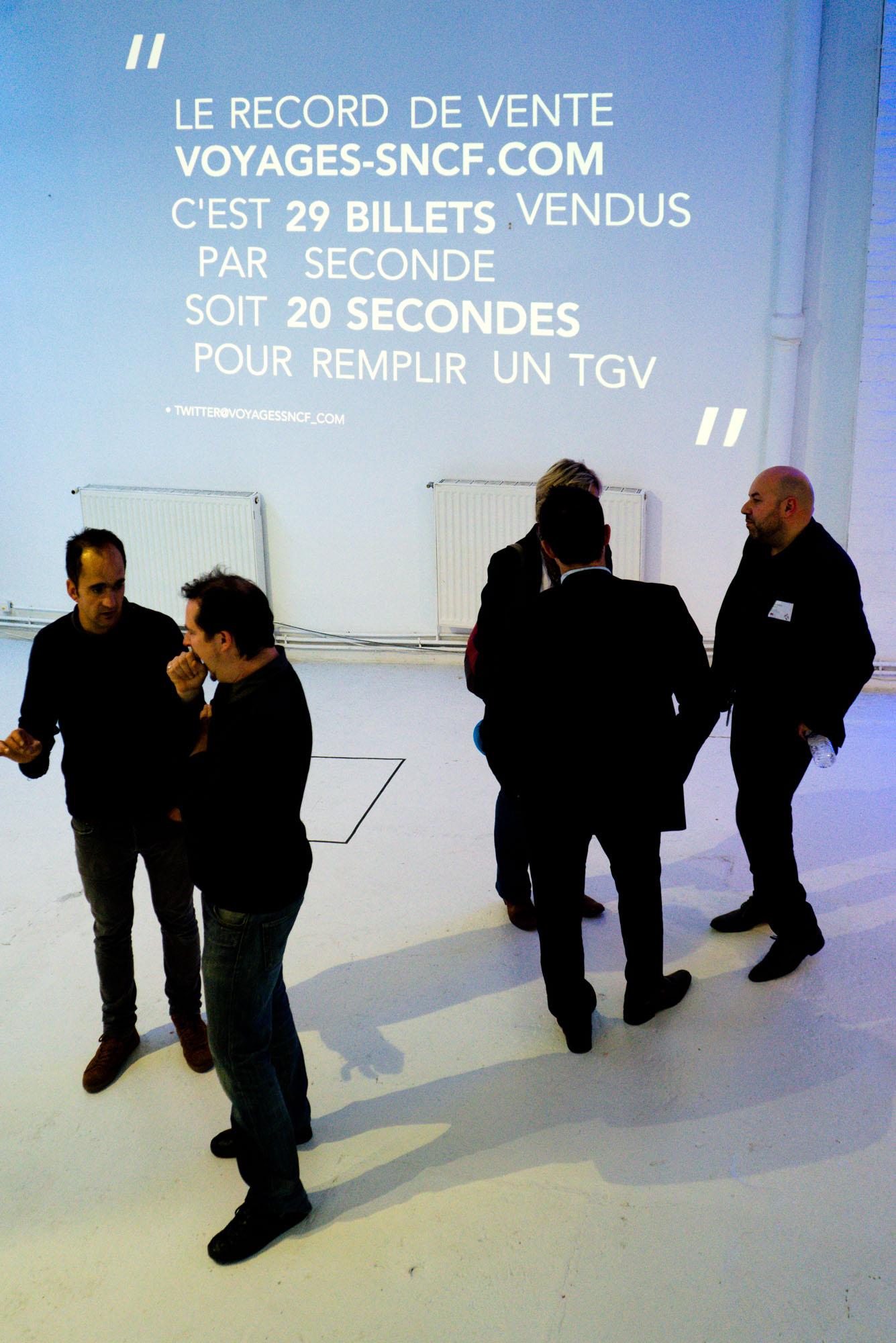 Photographie d'homme habillé en noir devant une projection de statistiques SNCF
