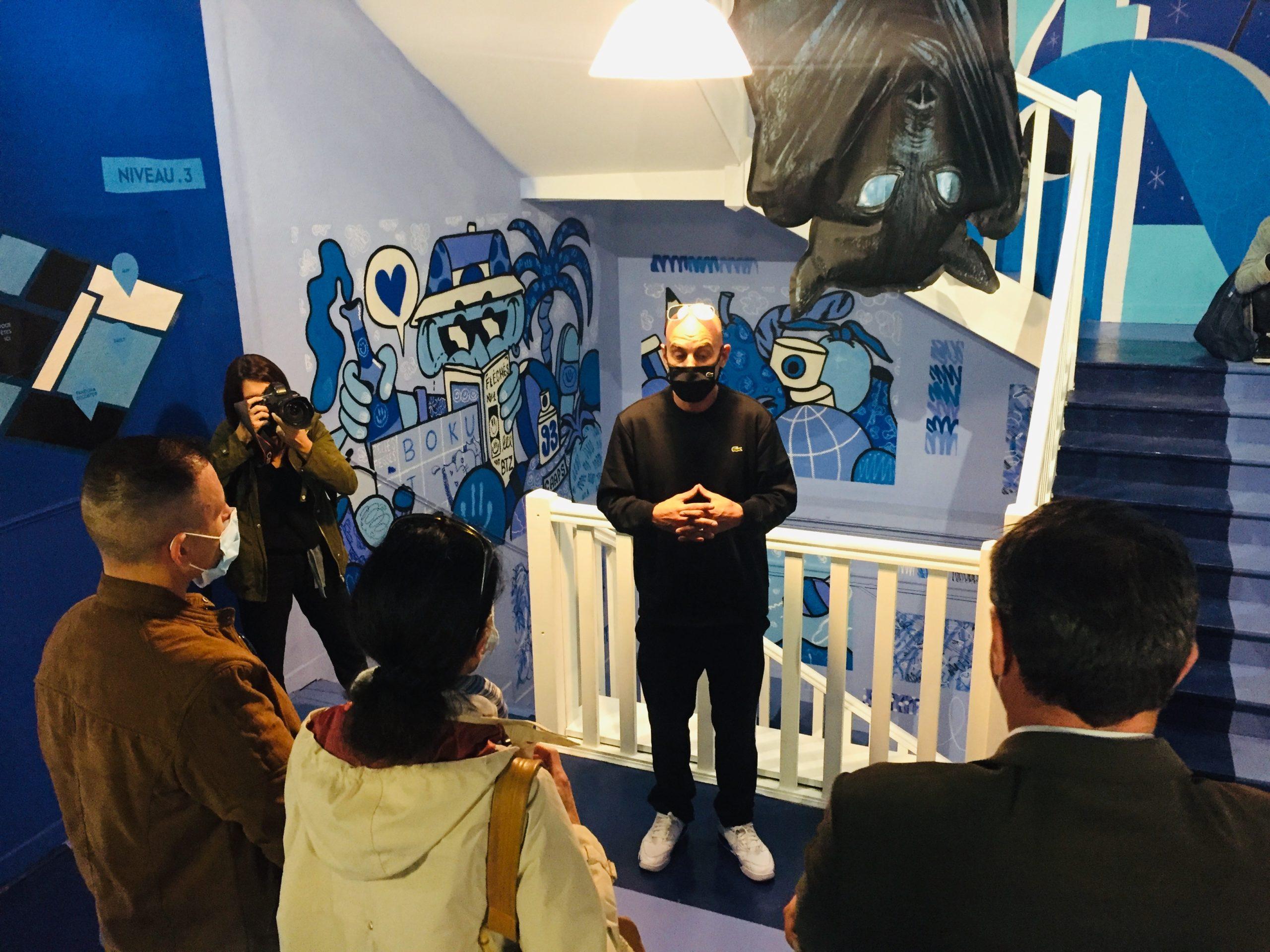 Interviews de Grems lors de l'inauguration du Colorama street art festival 2020, il est situé au centre masqué avec des journalistes autours et au milieu d'oeuvres de l'exposition