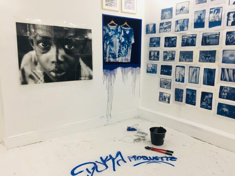 Salle blanche avec des photographies sur les murs de personnes et une grande d'un enfant avec des outils sur le sol et de la peinture bleu qui coule sur le mur