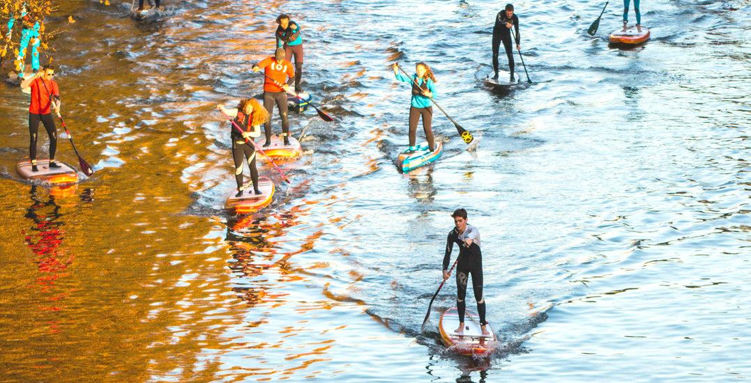 Dizaine de personnes en paddle sur l'eau en train de ramer sur une rivière calme