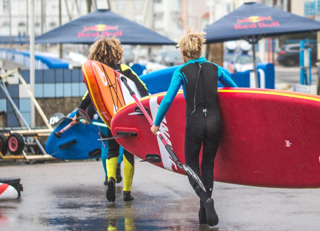 Deux femmes en combinaisons aquatique qui avancent avec leur paddles sous le bras et rame à la main