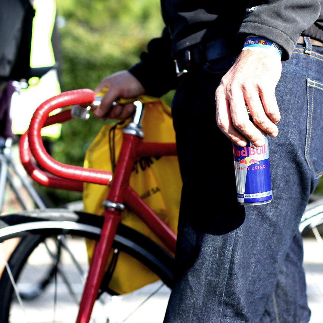 Gros plan sur une canette de redbull dans les main d'un homme tenant son vélo