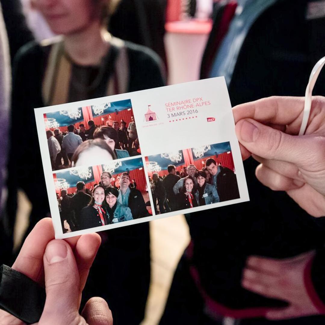 Personne tenant des photographies souvenir de la journée d'atelier au cirque de la SNCF