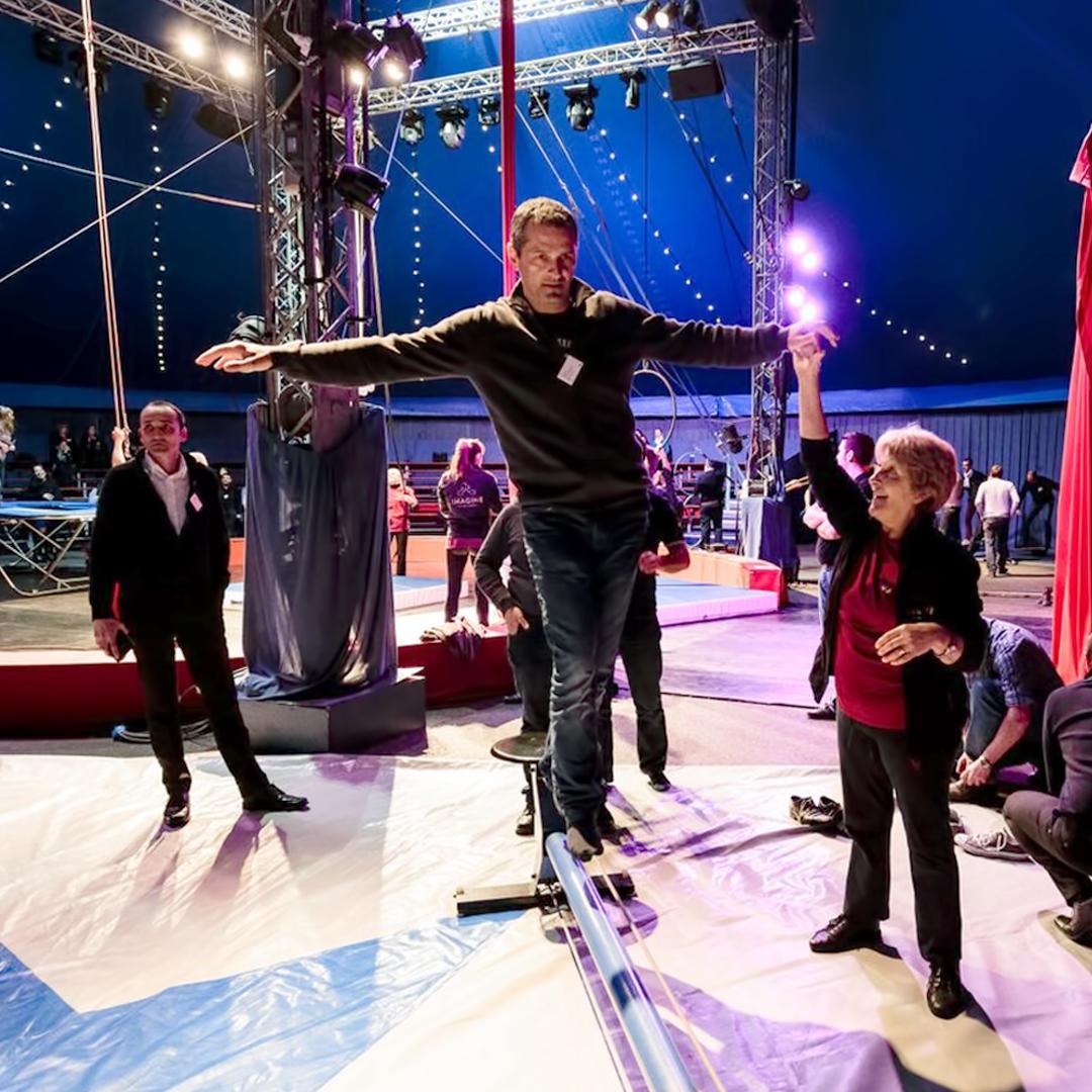 Homme qui apprend à tenir en équilibre sur une poutre au milieu d'un chapiteau de cirque