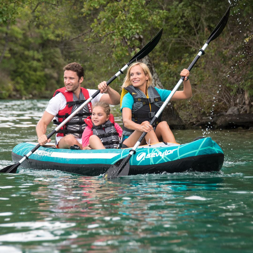 Une famille avec un père, une mère et une fille naviguent sur un kayak gonflable