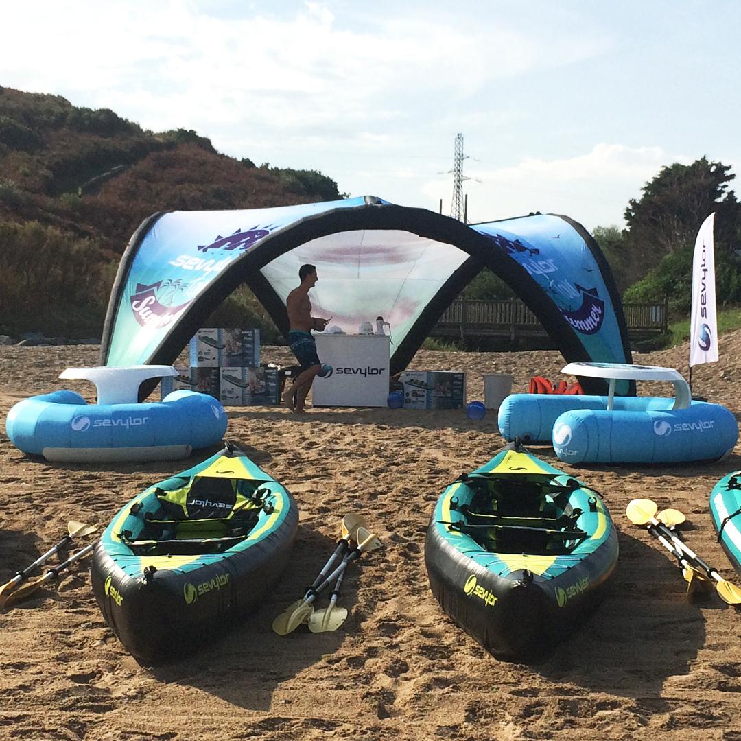 Une plage de sable avec des kayak gonflables alignés au sol et un stand en arrière plan