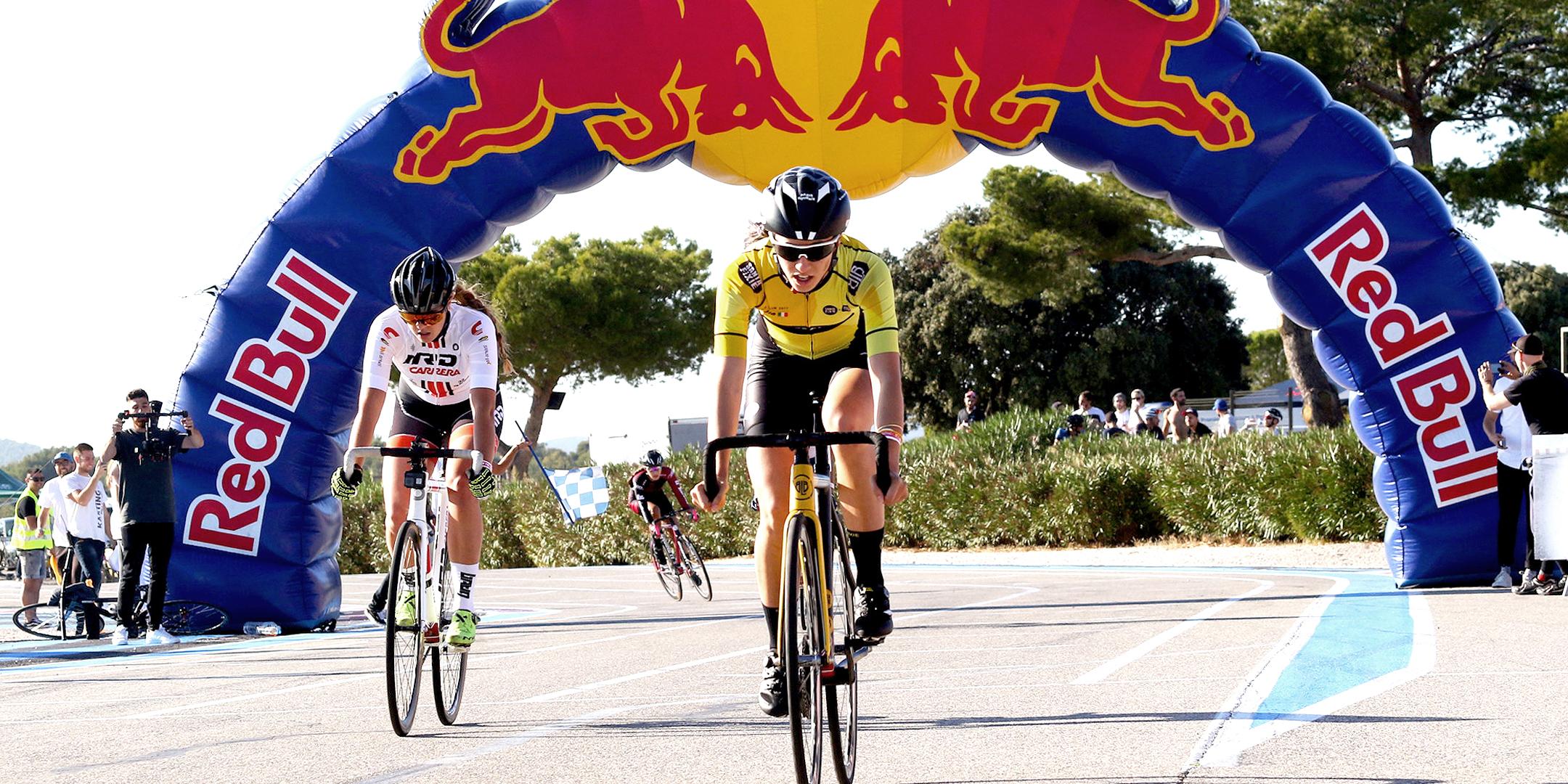 Cyclistes en train de passer sous une arche gonflable Red Bull géante