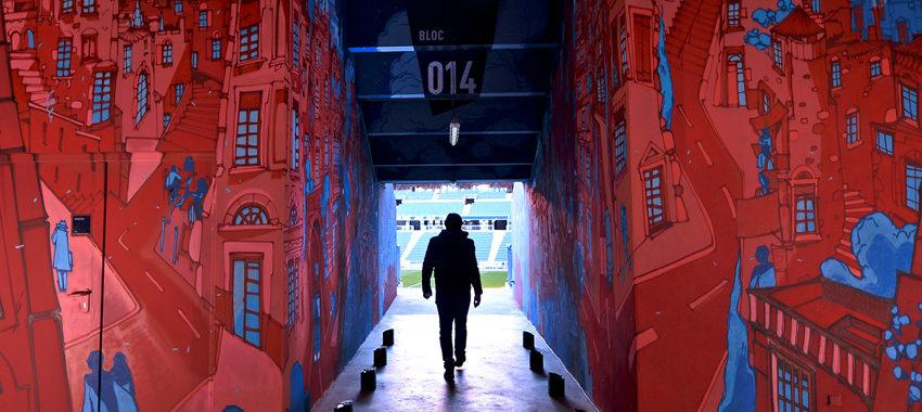 Homme qui avance dans un couleur taggé des deux côtés par un artiste graffeur au groupama Stadium de Lyon