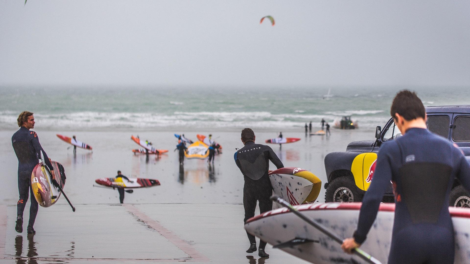 Paul Foulonneau avec son paddle et d'autres personnes sur la plage par mauvais temps