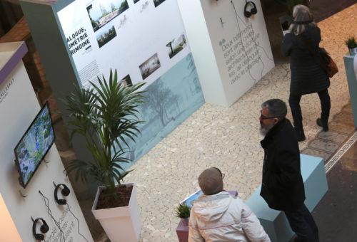 Personnes prenant connaissance des informations sur des corners de présentation de programmes immobiliers pour les thermes de la ville d'Aix-les-Bains