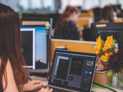Femme travaillant sur un pc portable sur un bureau avec des fleurs