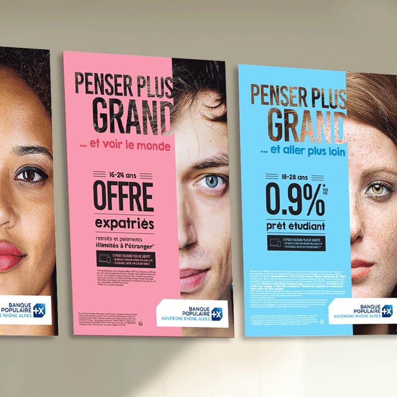 Affiches de la campagne jeunes Banque Populaire affichées sur un mur d'agence : une affiche jaune, une autre rose et une dernière bleue