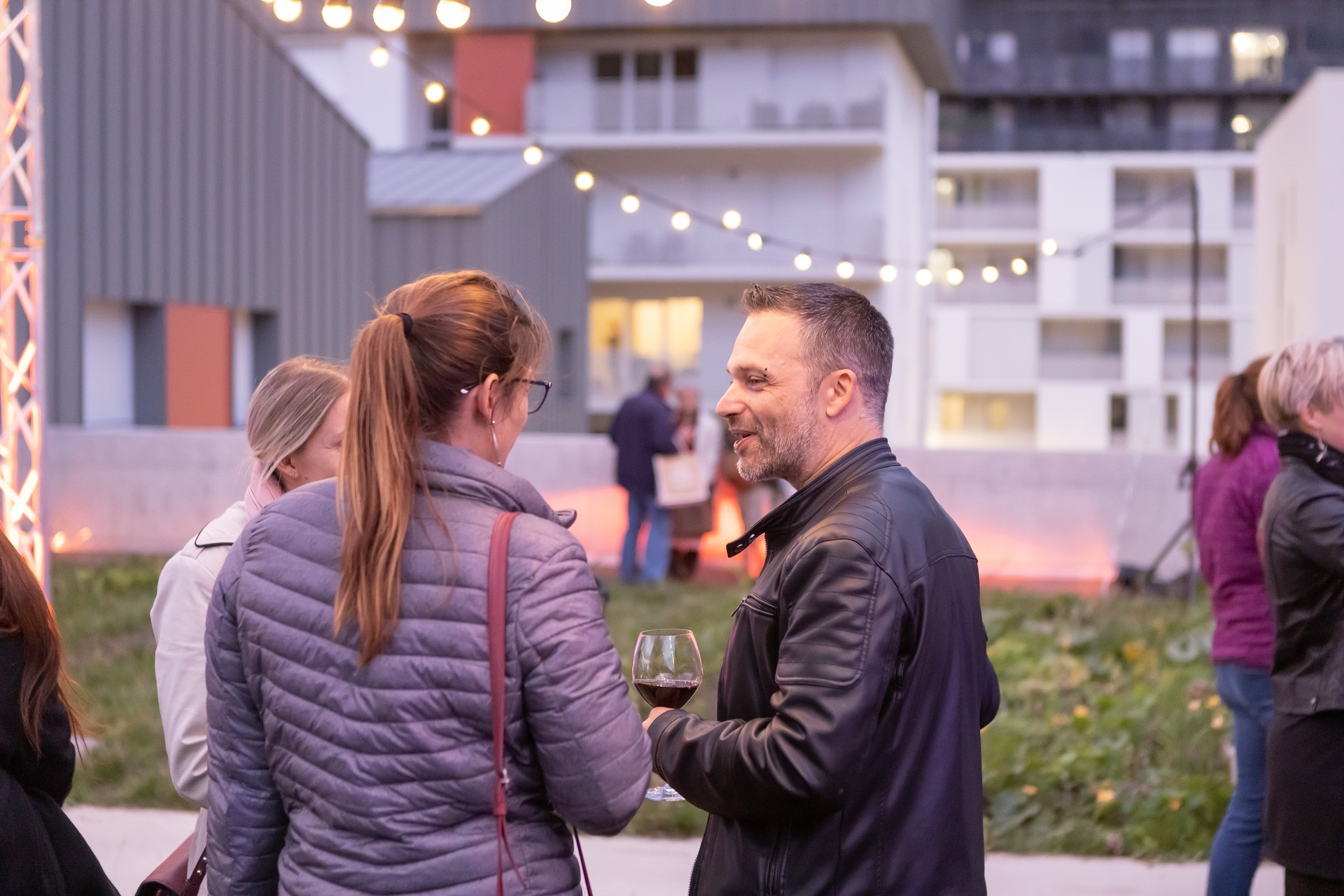 Résidents de la résidence immobilière Bouygues Immobilier discutant autour d'un verre convivial