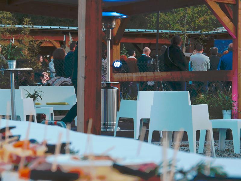 Personnes écoutant un discours devant un buffet et du mobilier événementiel extérieur