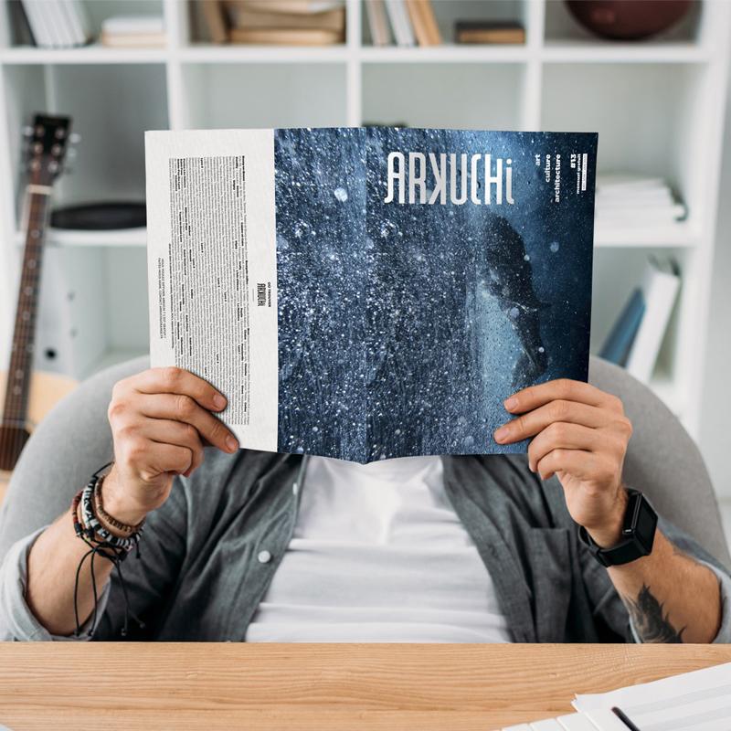 Homme dans un bureau tenant le magazine Arkuchi devant son visage avec une guitare et un bibliothèque en fond