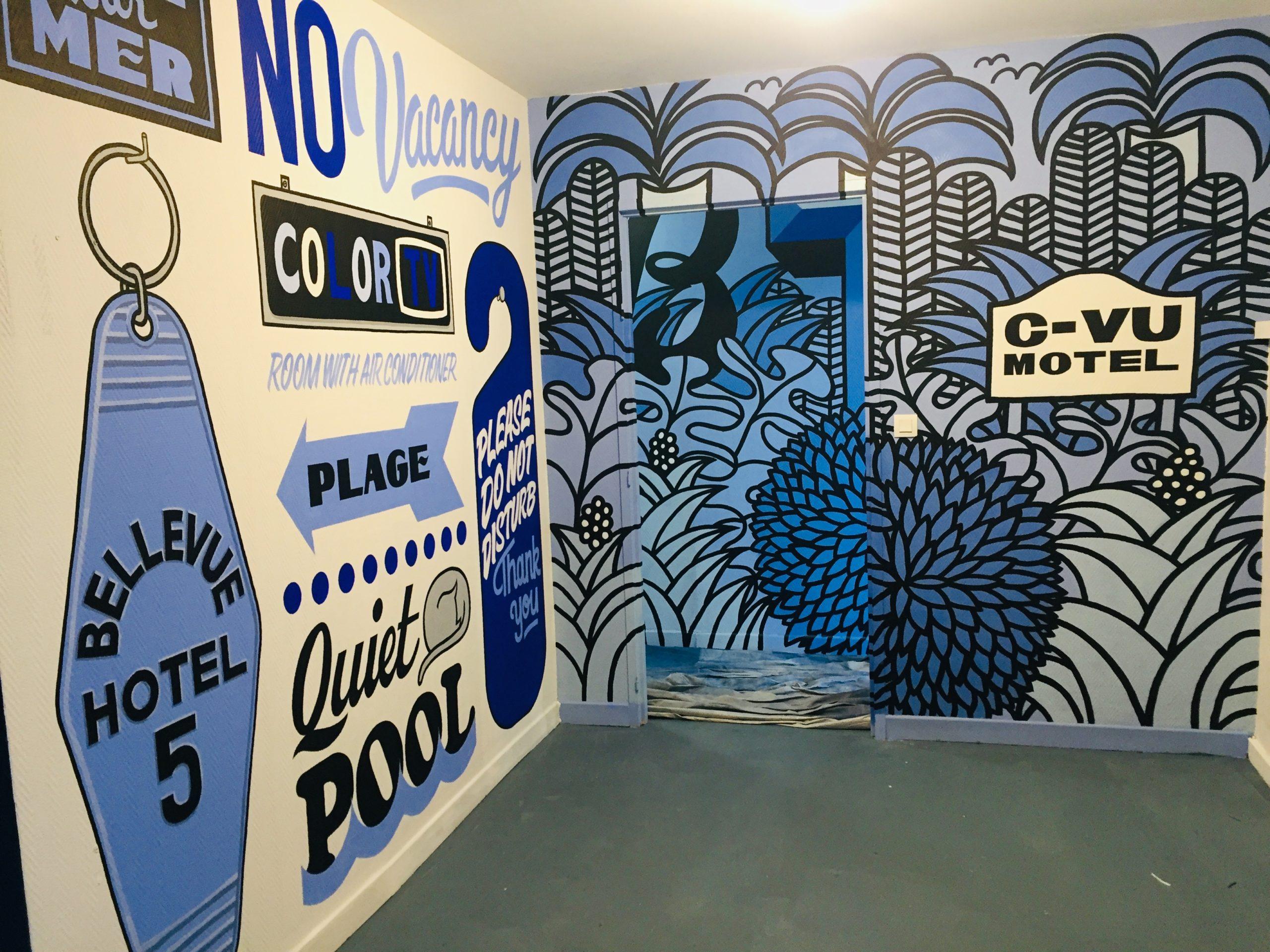 Salle du Colorama Festival avec des dessins bleu sur les murs sous forme de feuille et de panneaux de signalisation