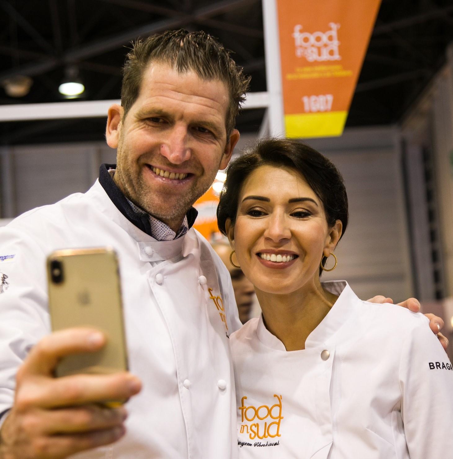 Une homme chef et une femme cheffe prenant un selfie au salon Food In Sud