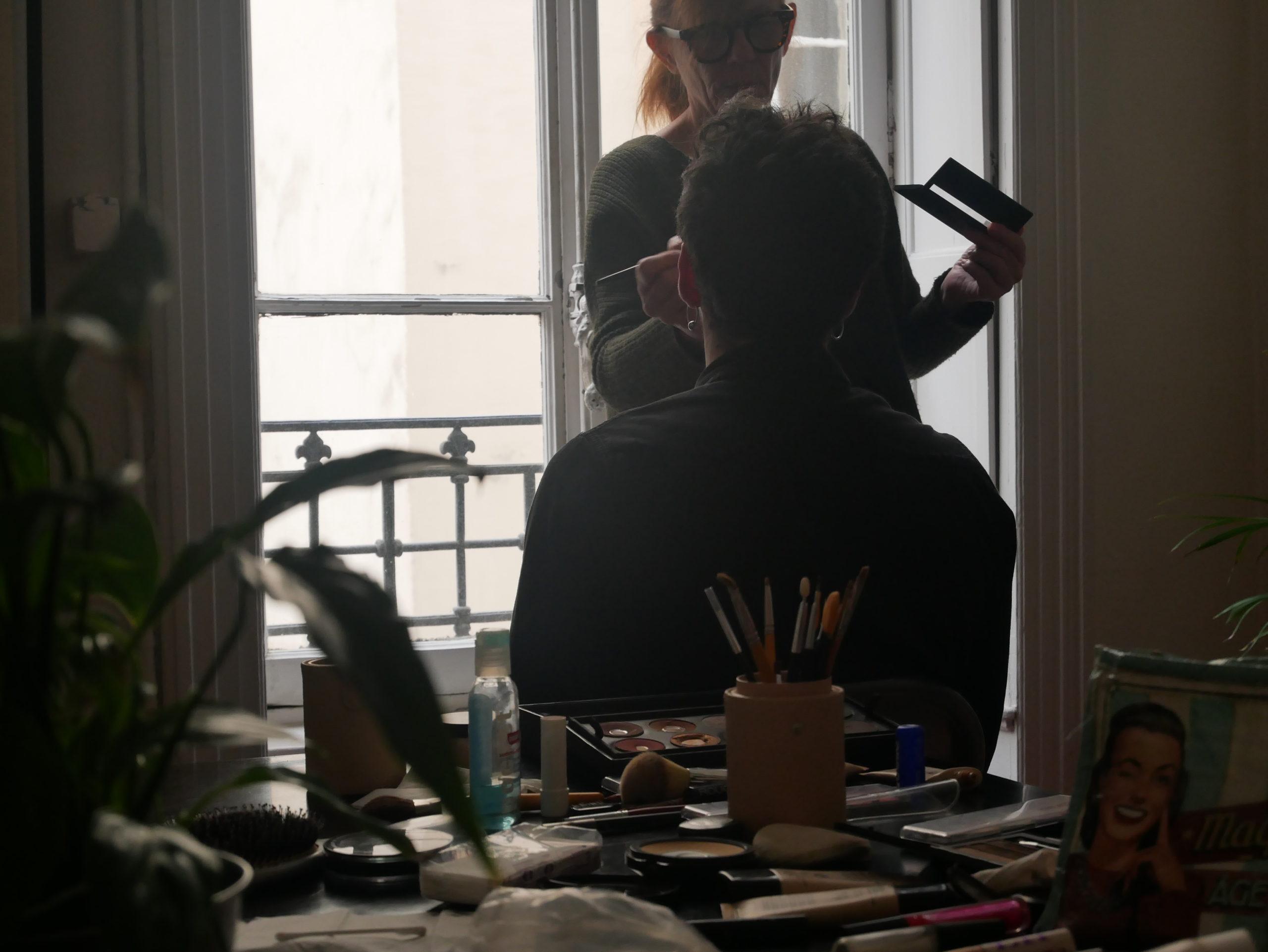 Séance de maquillage pour le shooting photo de l'agence avec accessoire en premier plan étalé sur une table et personne de dos se faisant maquiller
