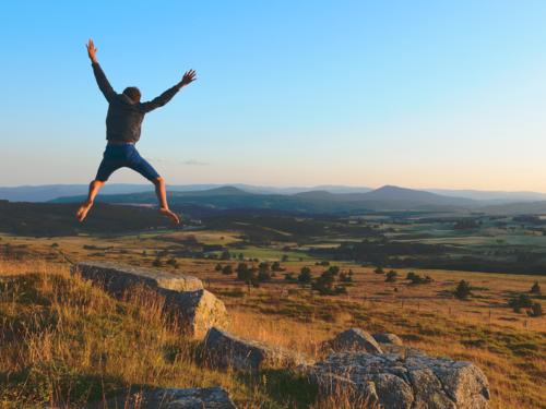 Personne sautant devant un paysage rhonalpins, les monts ardéchoix illustrant le carnet de tendances AURA Tourisme