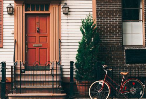 Porte d'entrée d'une maison mitoyenne de couleur brique avec vélo positionné devant pour parler de notre client Homeserve