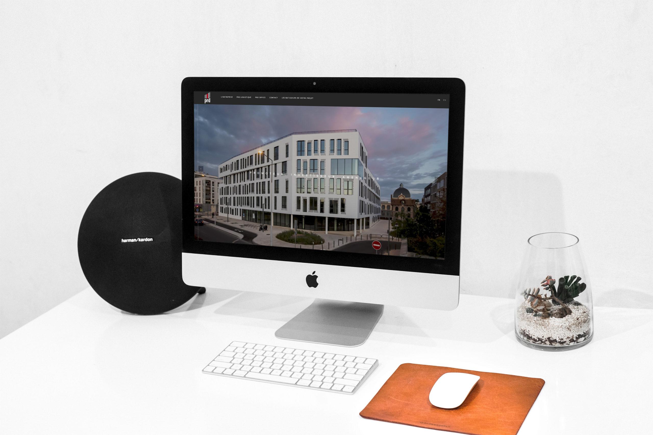 Mise en situation du site internet de PRD sur un ordinateur fixe de type MAC avec une enceinte et une plante verte à côté