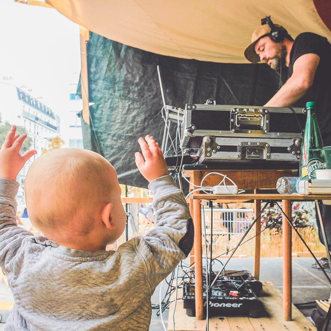 Jeune enfant au premier plan les bras levés devant un DJ sur scène en train de faire de la musique