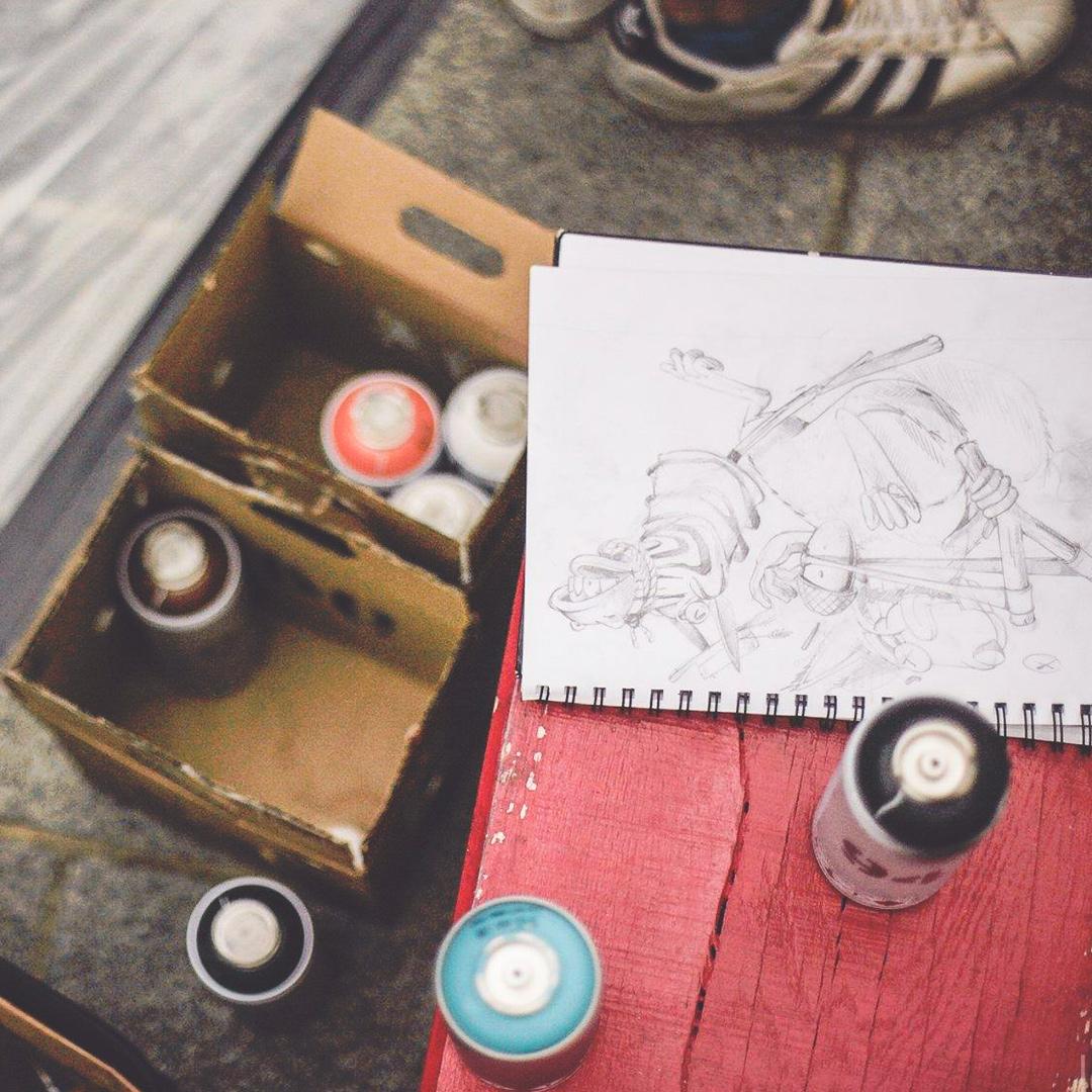 Gros plans sur le sol avec des basket adidas, des bombes de peintures de plusieurs couleurs dans une caisse et un dessin au crayon de papier qui va devenir une fresque