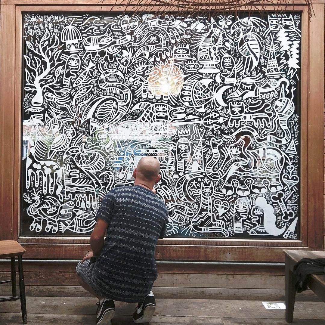 Artiste graffeur en train de peindre un fresque en blanc sur une vitre teintée noire
