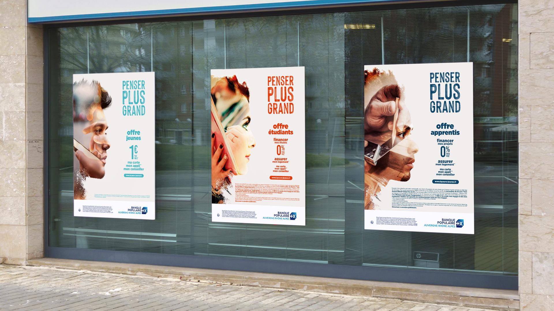 Trois affiches bleu turquoise, orange et bleu marine affichées sur les murs de la banque pour la campagne de communication jeune 2020