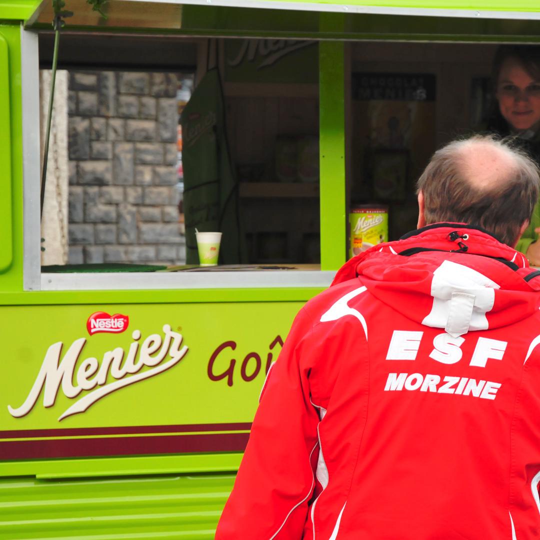 Gros plan sur un moniteur de ski de la station de Morzine devant le stand chocolat menier devant un camion vert fluo de distribution de chocolats chauds