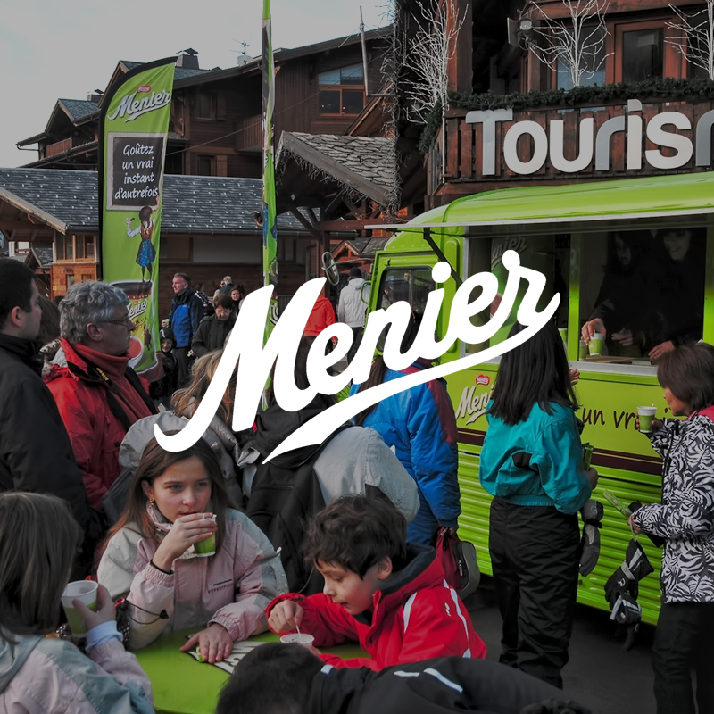 Roadshow chocolat menier en bas des pistes de ski avec un camion vert fluo de distribution de chocolats chauds