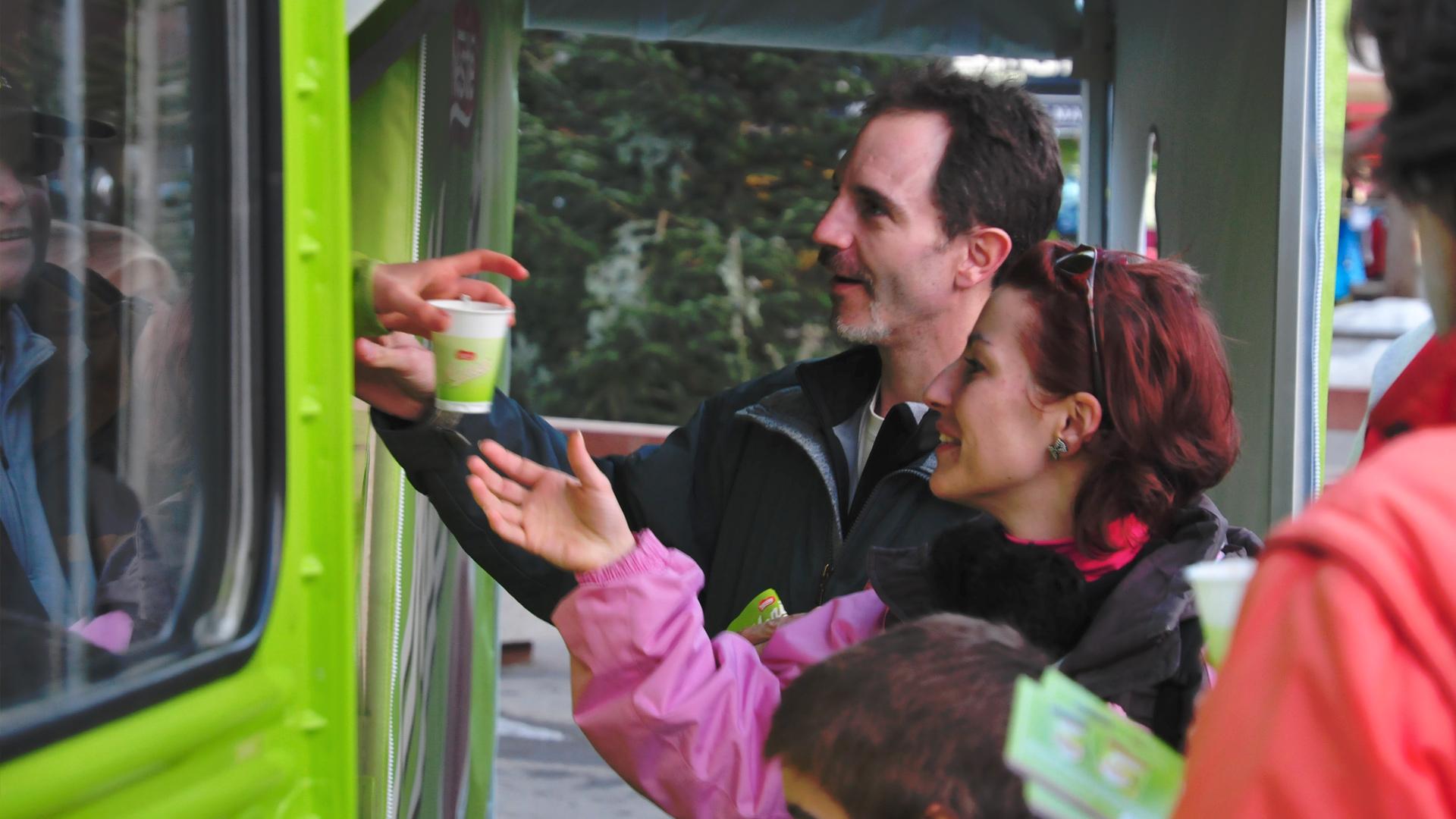 Personnes récupèrant leur chocolat menier auprès du stand camion vert en bas des pistes de ski