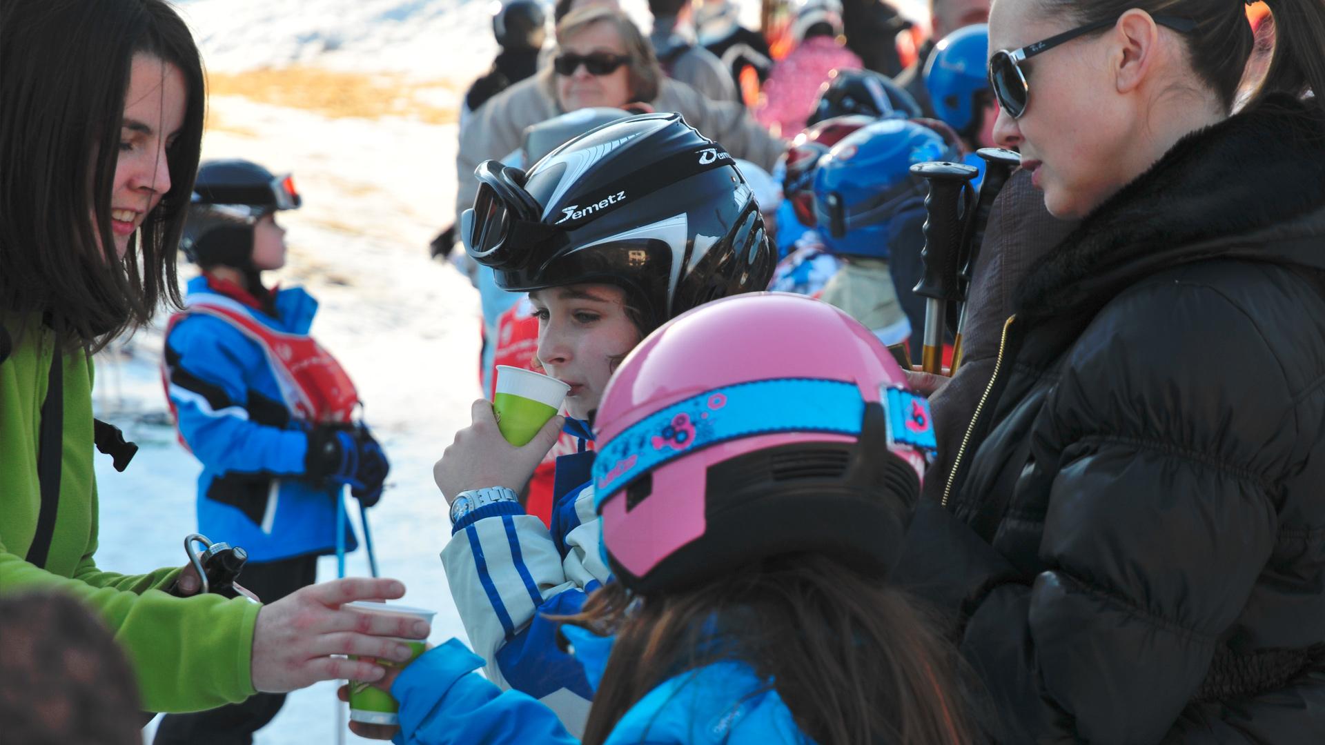 Une famille qui déguste un chocolat chaud menier tendu par une animatrice commerciale en bas des pistes de la station de ski