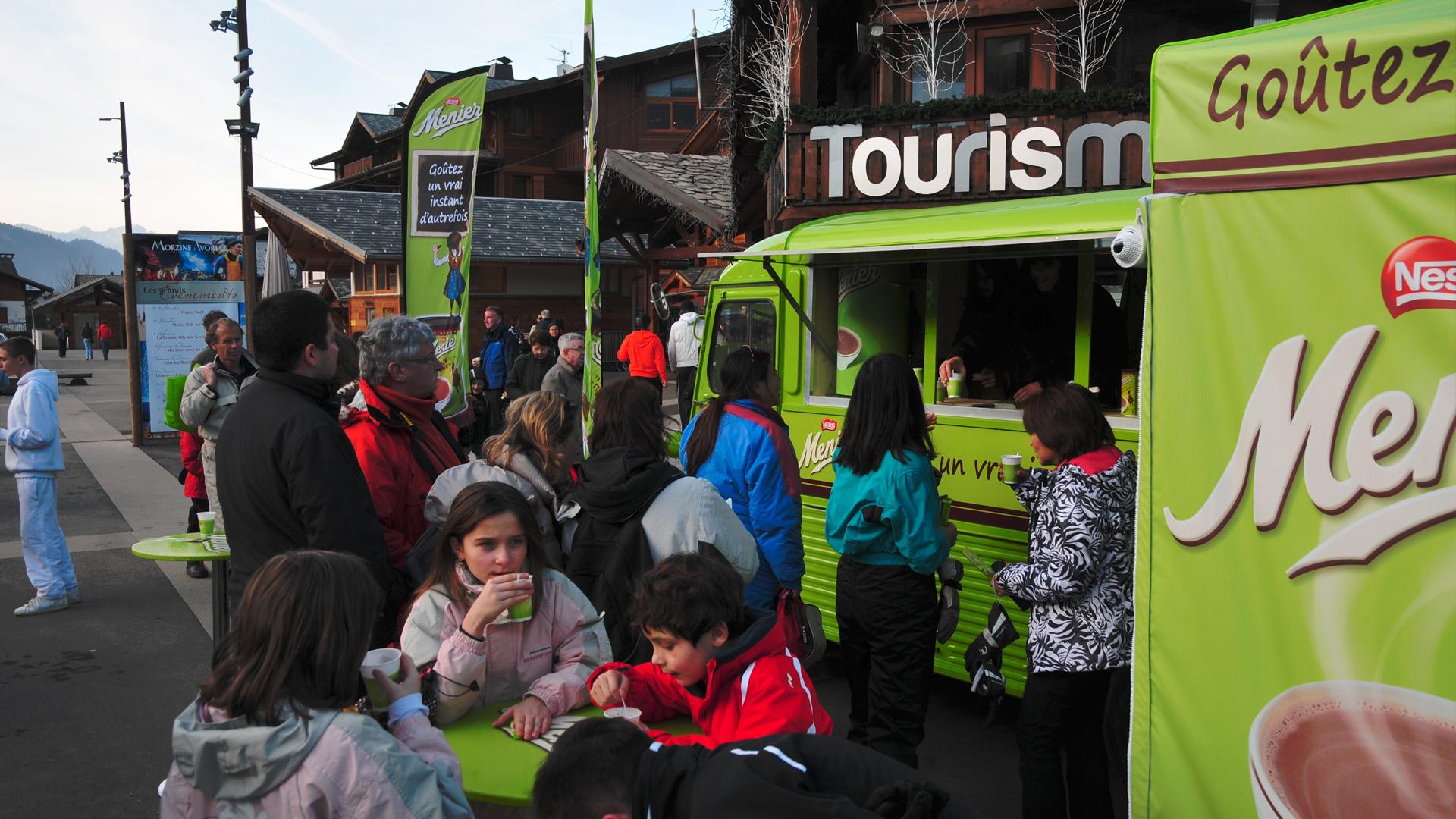 Chocolat menier en bas des pistes de ski avec un camion vert fluo de distribution de chocolats chauds