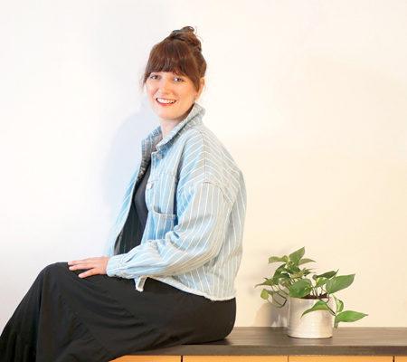Portrait de Claire notre nouvelle graphiste assise sur un meuble avec une plante verte