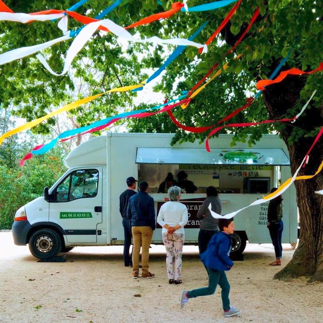 Personnes qui attendent devant un food truck pour commander à mange sous un arbres avec des rubans de toutes les couleurs au vent