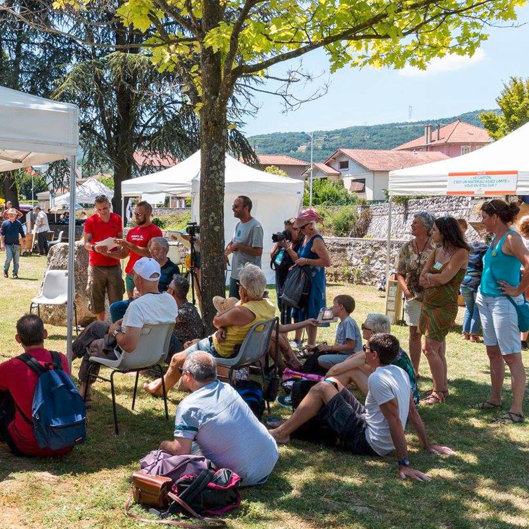 Plan large du village du Crussol Festival avec des personnes à l'ombre d'un arbre assis par terre
