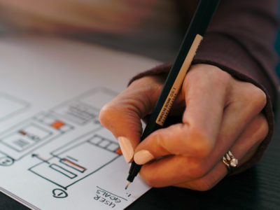 Main de femme tenant un stylo pour rédiger et réaliser des graphiques