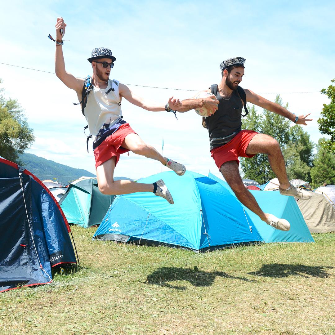 Duo d'homme en train de sauter en l'aire au milieu du camping du festival Musilac