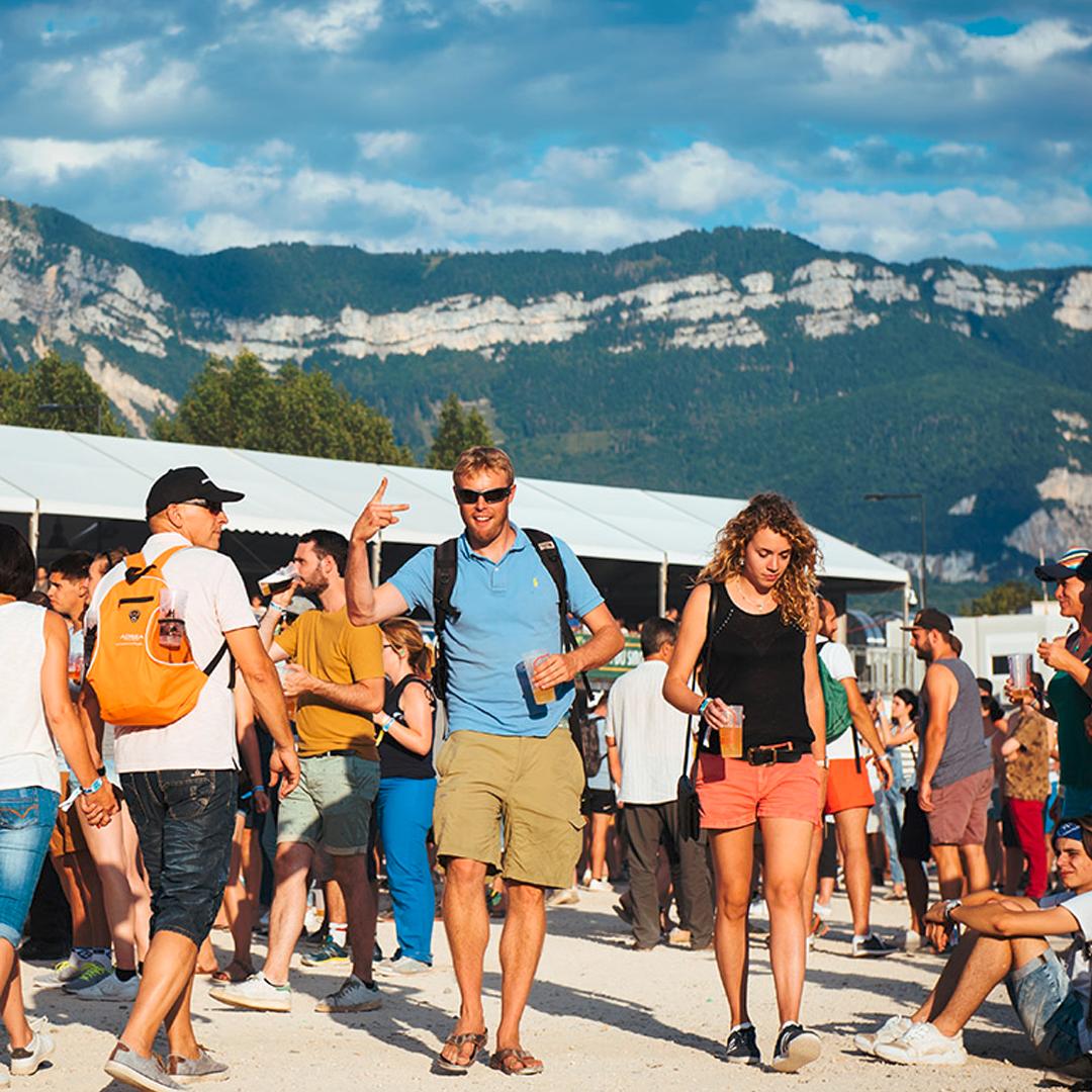 Des personnes devant la buvette qui se déplace avec leur bière à la main sur fond de montagne