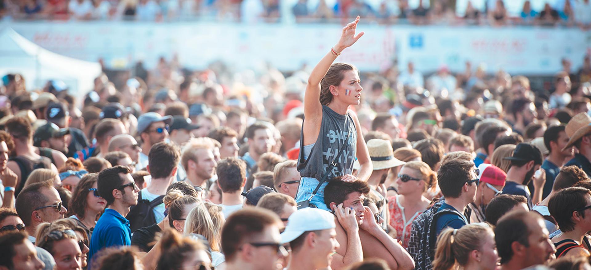 Photographie d'une foule dans la fosse d'un concert avec une jeune femme au milieu sur les épaules d'un jeune homme