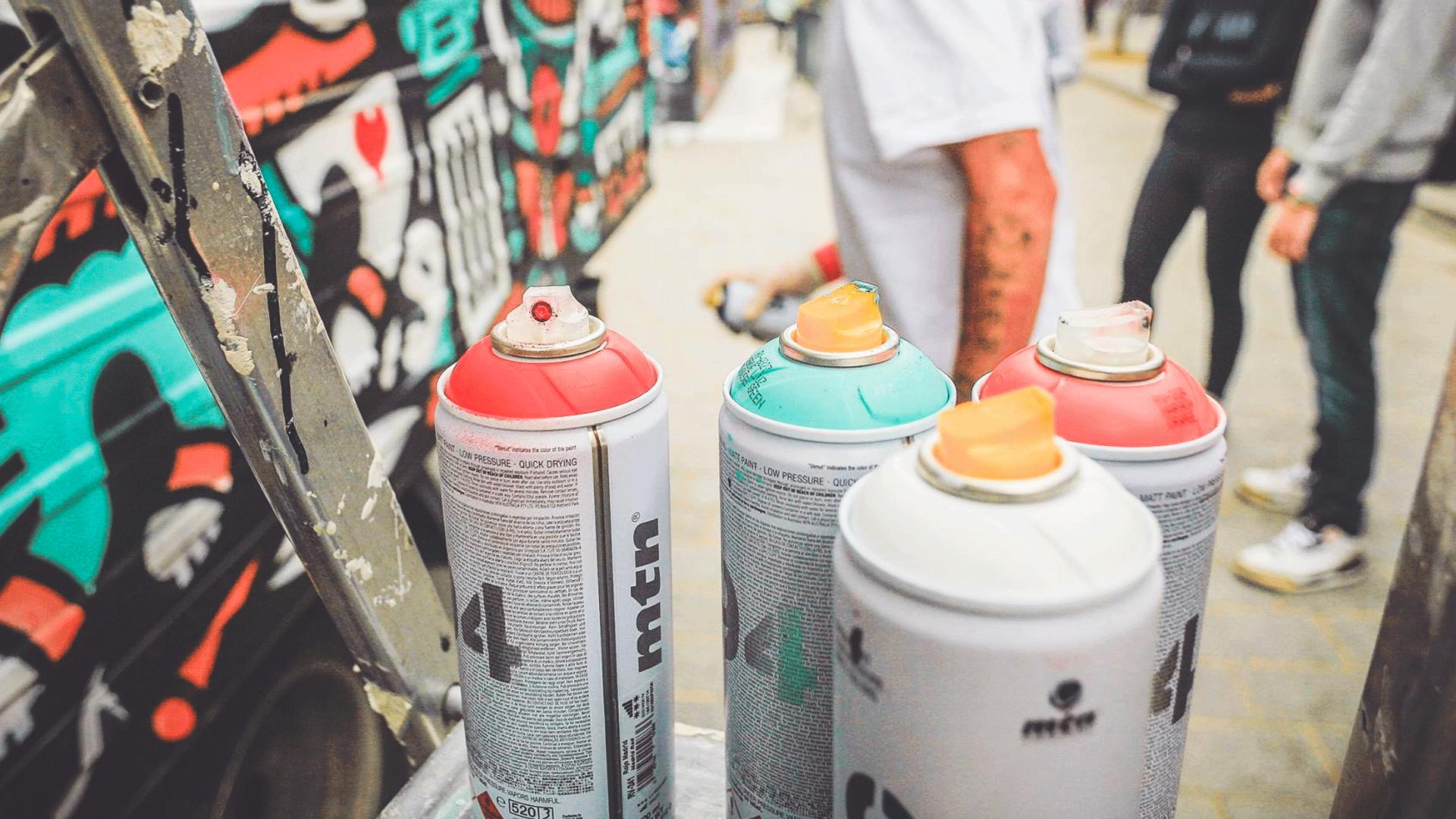Homme derrière des bombes de peinture qui réalise une fresque sur un mur pour le festival Top To Bottom