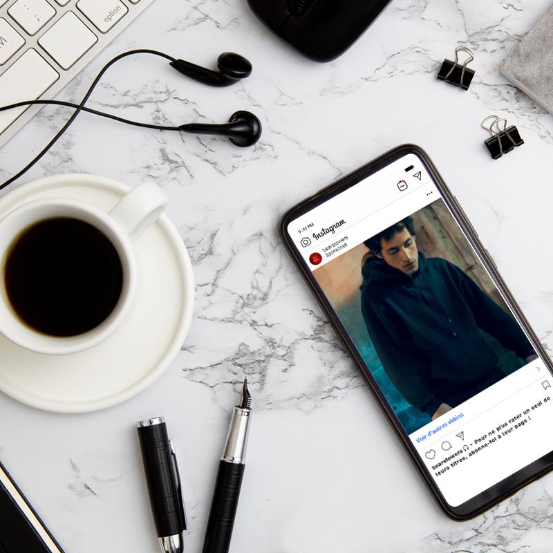 Téléphone mobile ouvert sur Instagram avec un café, des écouteurs, des stylos et un clavier d'ordinateur mac