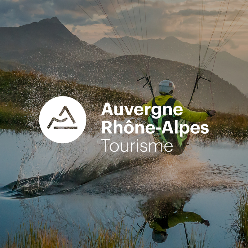 Homme en deltaplane sur un lac avec logo Aura Tourisme en blanc