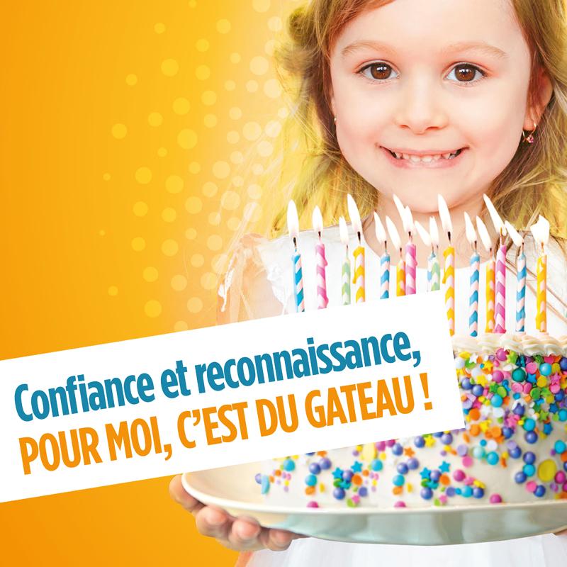 Gros plan sur une petite fille qui tient un gateau d'anniversaire avec plein de bougies dessus