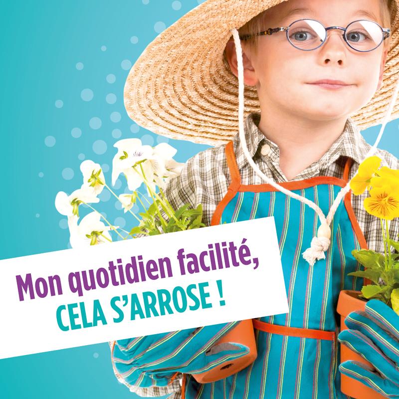 Gros plan sur un petit garçon à lunette en tenue de jardinier qui tient de pots de fleurs dans ses mains