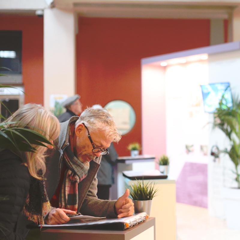 Photographie avec personnes dans le hall des Thermes d'aix les bains devant des panneaux de présentation du projet de réhabilitation