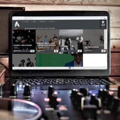 Ordinateur ouvert avec tablette de mixage et sur l'écran le site internet les abattoirs