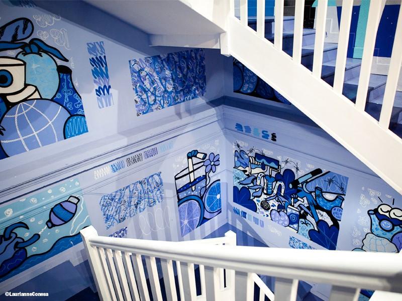 Cage d'escalier de l'hotel colorama de Biarritz avec des dessins bleu de gobelet, d'eau et des oeuvres abstraites sur les murs autour d'une rampe d'escalier blanche immaculée