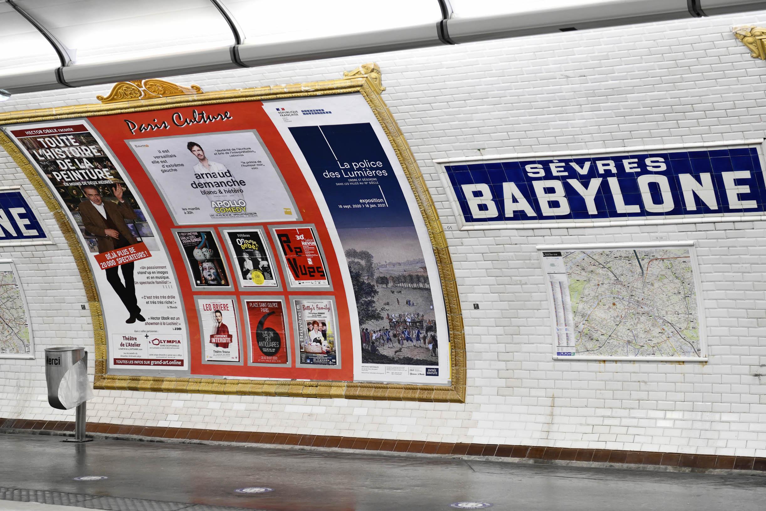 Quai de métro parisien Sevres Babylone avec affichage d'une campagne publicitaire sur le mur de carreaux blanc d'Arnaud Demanche